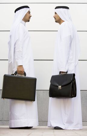dishdashas: Two businessmen standing outdoors with briefcases