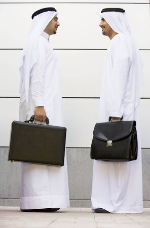 Two businessmen standing outdoors with briefcases smiling