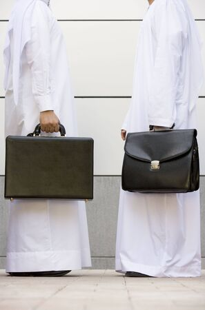 thawbs: Two businessmen standing outdoors with briefcases