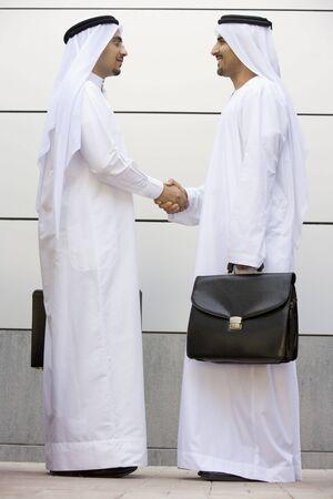 manos estrechadas: Dos hombres de negocios de pie al aire libre con maletines agitando las manos sonrientes  Foto de archivo