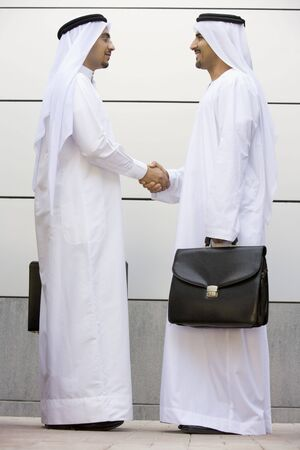 Two businessmen standing outdoors with briefcases shaking hands smiling