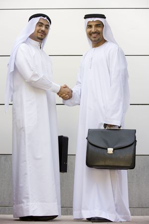 Two businessmen standing outdoors with briefcases shaking hands and smiling Stock Photo