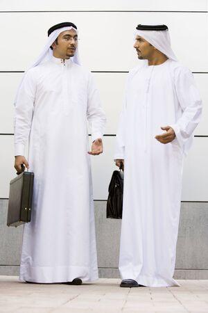 thawbs: Dos hombres de negocios de pie afuera hablando con maletines  Foto de archivo
