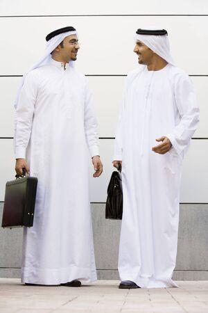 thobes: Dos hombres de negocios de pie al aire libre con maletines de hablar y sonre�r