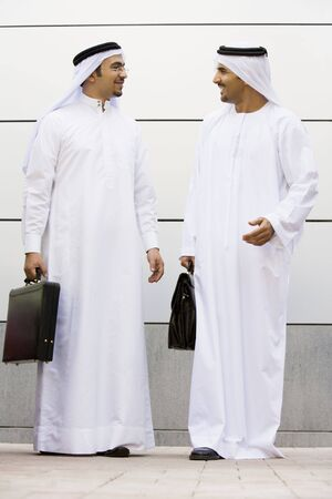Two businessmen standing outdoors with briefcases talking and smiling photo