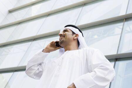 thawbs: Empresario de pie afuera de la construcci�n en el tel�fono port�til sonriente (atenci�n selectiva)