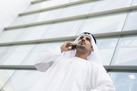 thobes: Businessman standing outdoors by building on cellular phone (selective focus)