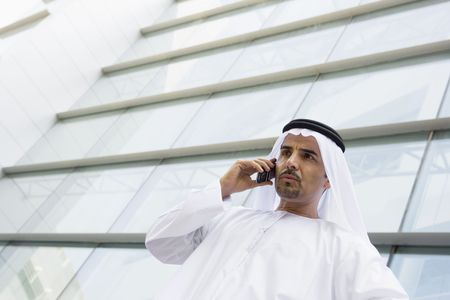 Businessman standing outdoors by building on cellular phone (selective focus)