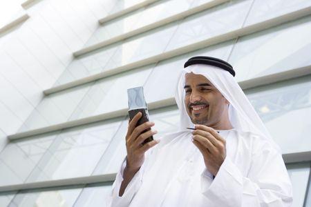thobes: Empresario de pie afuera de edificio utilizando asistente digital personal y sonriente (atenci�n selectiva)
