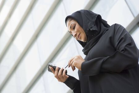 jilaabah: Businesswoman outdoors by building using personal digital assistant and smiling (selective focus) Stock Photo