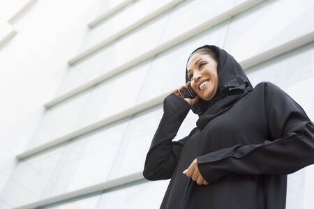 jilaabah: Businesswoman outdoors by building using cellular phone and smiling (selective focus)