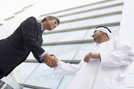 Two businessmen outdoors by building shaking hands and smiling (high keyselective focus)