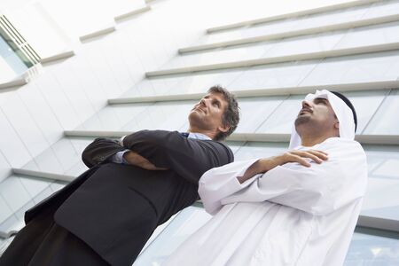 Two businessmen standing outdoors by building (high keyselective focus)