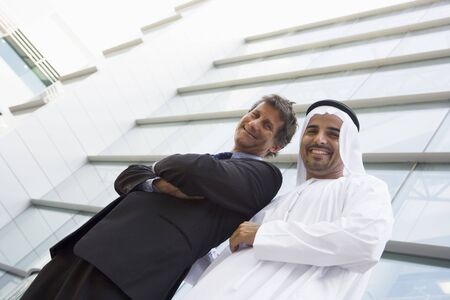 Two businessmen standing outdoors by building (high keyselective focus) photo