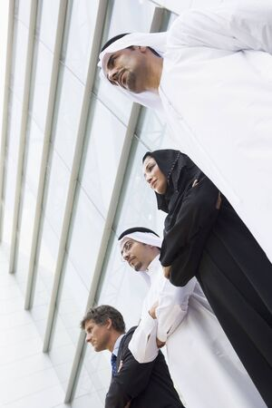agal: Four businesspeople standing outdoors by building (selective focus)