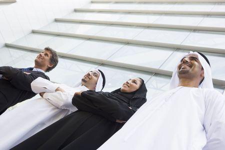 thawbs: Cuatro empresarios de pie al aire libre mediante la creaci�n de sonrientes (atenci�n selectiva)  Foto de archivo