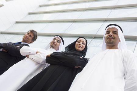 thobes: Cuatro empresarios de pie al aire libre mediante la creaci�n de sonrientes (atenci�n selectiva)  Foto de archivo
