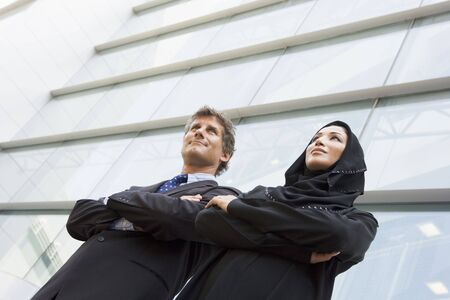 east meets west: Two businesspeople standing outdoors by building smiling (selective focus)