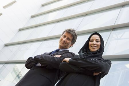 Two businesspeople standing outdoors by building smiling (selective focus)
