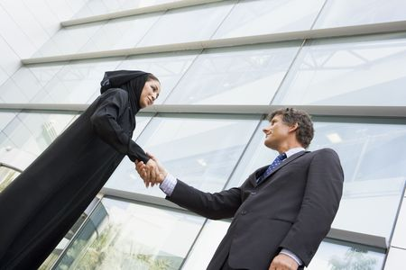 east meets west: Two businesspeople standing outdoors by building shaking hands and smiling (selective focus)