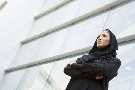 jilaabah: Businesswoman standing outdoors by building (selective focus) Stock Photo