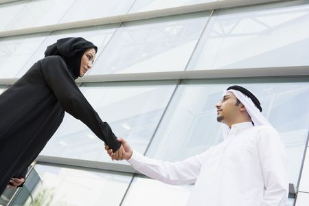 Two businesspeople outdoors by building shaking hands