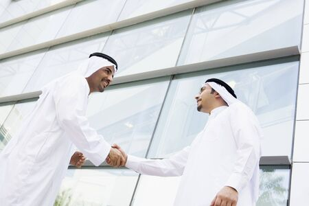 thawbs: Two businessmen outdoors by building shaking hands and smiling