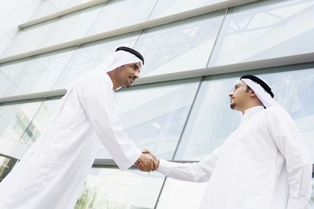 manos estrechadas: Dos hombres de negocios al aire libre mediante la construcci�n de darse la mano