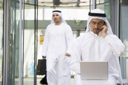 thawbs: Empresario al aire libre con el ordenador port�til por tel�fono celular con el hombre de negocios a pie en el fondo (enfoque selectivo)