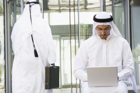 thawbs: Empresario al aire libre, utilizando equipo port�til con el empresario para caminar en el fondo (enfoque selectivo)  Foto de archivo