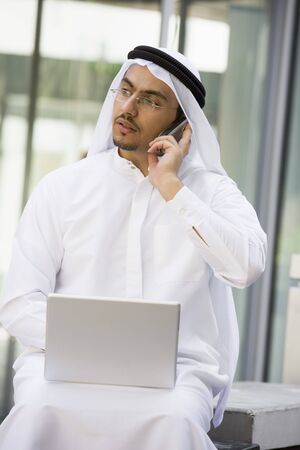 Businessman outdoors with laptop using cellular phone by building (selective focus)