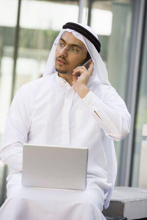 thawbs: Empresario al aire libre con el ordenador port�til utilizando el tel�fono port�til de edificio (atenci�n selectiva)
