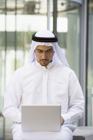 thawbs: Empresario sesi�n al aire libre con el ordenador port�til mediante la construcci�n de (atenci�n selectiva)  Foto de archivo