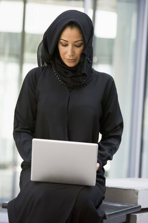 jilaabah: Businesswoman sitting outdoors with laptop by building (selective focus)