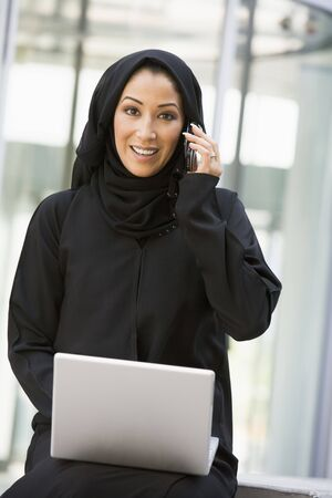 jilaabah: Businesswoman sitting outdoors by building with laptop using cellular phone smiling (selective focus)