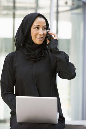 mobilephones: Businesswoman sitting outdoors by building with laptop using cellular phone smiling (selective focus)