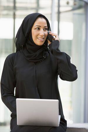 Empresaria sesión al aire libre mediante la construcción de ordenadores portátiles con teléfonos celulares utilizando sonriente (atención selectiva)  Foto de archivo - 3171146