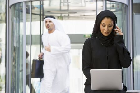 jilaabah: Businesswoman sitting outdoors by building with laptop using cellular phone with businessman running in background (selective focus)