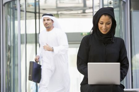 Businesswoman sitting outdoors by building with laptop smiling with businessman running in background (selective focus) photo