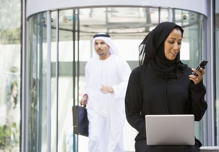 jilaabah: Businesswoman sitting outdoors by building with laptop holding cellular phone with businessman running in background (selective focus) Stock Photo