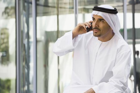 kanduras: Businessman sitting outdoors by building using cellular phone (selective focus) Stock Photo