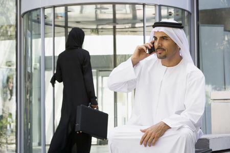 thawbs: Empresario sesi�n al aire libre mediante la construcci�n de utilizar tel�fonos celulares con negocios caminar en el fondo (enfoque selectivo)  Foto de archivo