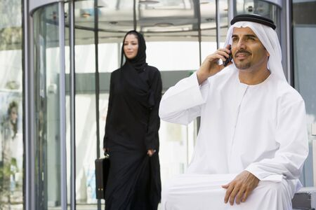 Businessman sitting outdoors by building using cellular phone with businesswoman walking in background (selective focus) photo