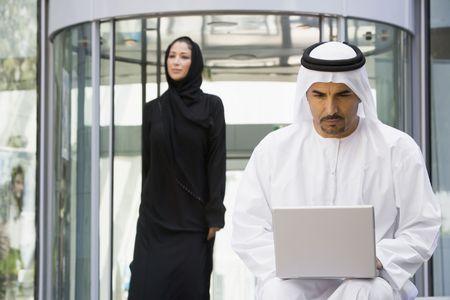 thawbs: Empresario sesi�n al aire libre mediante la construcci�n de utilizar ordenador port�til de negocios a pie en el fondo (enfoque selectivo)  Foto de archivo