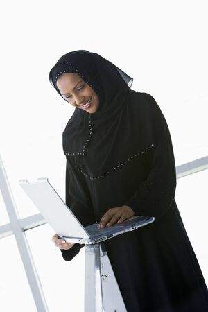 jilaabah: Woman indoors standing with laptop and smiling (high keyselective focus)
