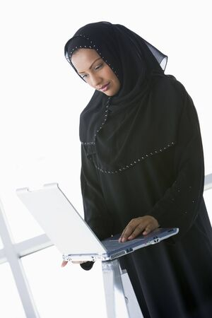 offset angles: Woman indoors standing with laptop (high keyselective focus)  Stock Photo