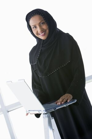 jilaabah: Woman indoors standing with laptop and smiling (high keyselective focus) Stock Photo