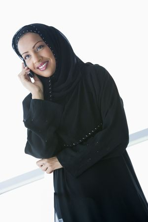 jilbab: Woman indoors using cellular phone and smiling (high keyselective focus)