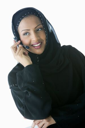 handsfree telephones: Woman indoors wearing headset and smiling (high keyselective focus) Stock Photo