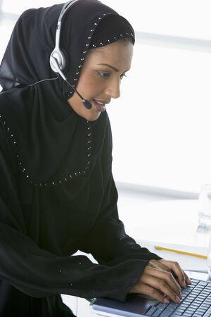 mobile headset: Mujer con el uso de auriculares port�til sonriente (clave de alta  selectiva enfoque)